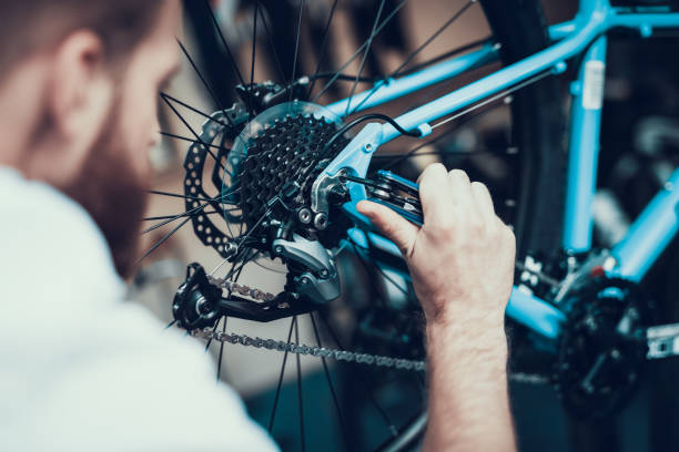 Bike Mechanic Repairs Bicycle in Workshop stock photo
