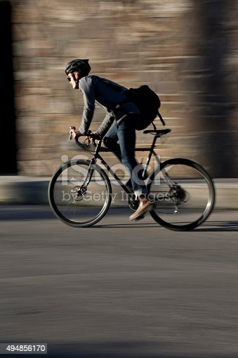 A male bike messenger rides along a busy street on a sunny morning.