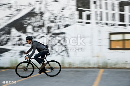 A male bike messenger rides through an alley and past a building covered with graffiti.
