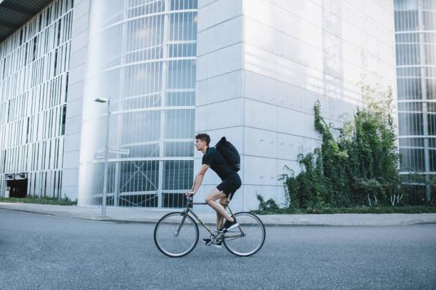 Bike messenger riding down the street. stock photo