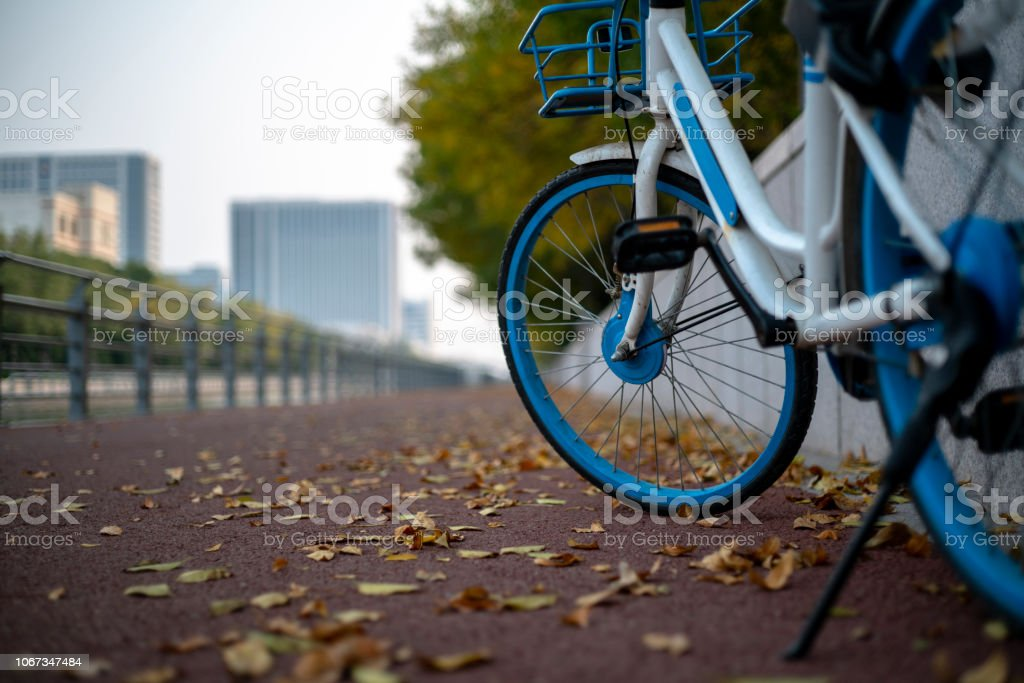 bike on sidewalk in autumn stock photo