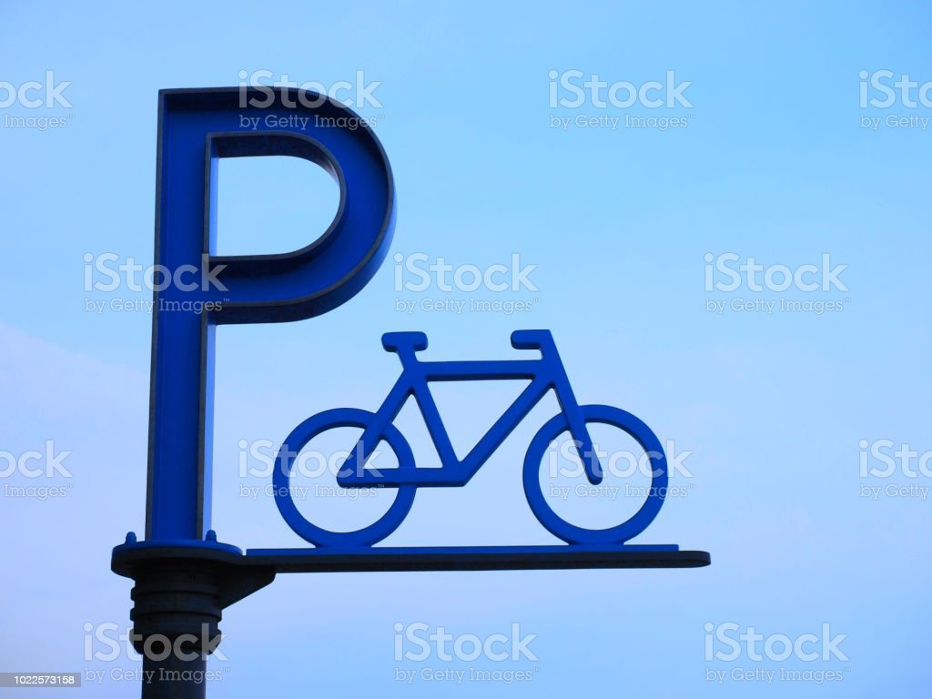 Bike Parking Sign against Blue Sky Background stock photo