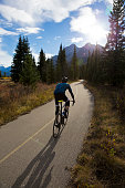A male road cyclist rides a designated bike path in the Rocky Mountains of Canada. He is riding straight into the sun and standing as he pedals his road bike.