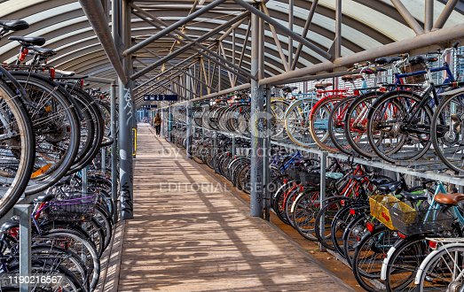Bike rack by Aarhus, Denmark railroad station. It is a roofed rack that is free to use and located next to the station in the centre of Aarhus, the second largest city of Denmark. One person is visible at the far end of the shed.