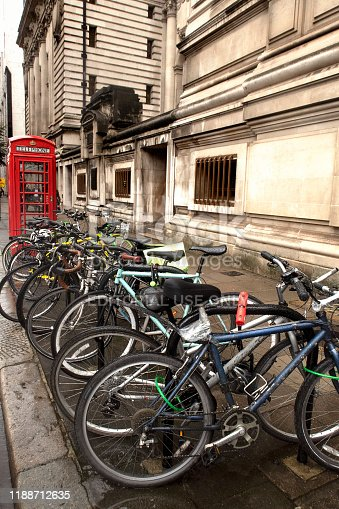 commuters' bicycles locked to bike racks on a sidewalk in the downtown area in the West End, in London, England, with an iconic English red public telephone booth in the background
