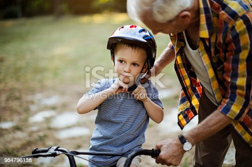 Devoted grandfather teaching a grandchild how to ride a bike