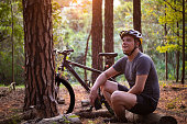istock Bike rider at a pine trees forest. 1278459908