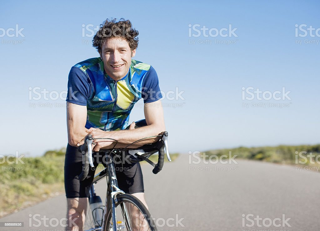 Bike rider resting on bicycle in remote area royalty-free stock photo
