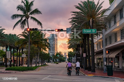 In Miami Beach, United States two people ride bikes off Ocean Drive in South Beach as the sunsets during the Coronavirus pandemic.