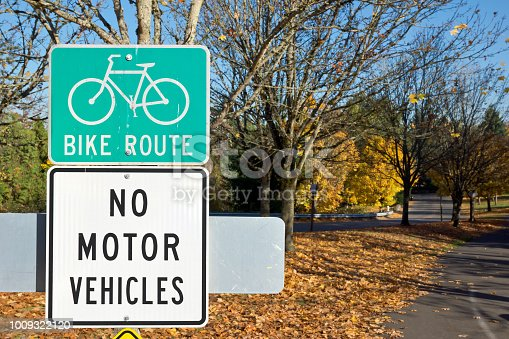 The season is autumn, thus this city sign gives awareness of a bike route and no motor vehicles allow.