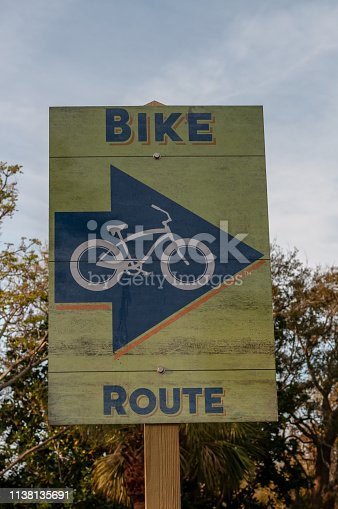 Wooden bike route sign with arrow pointing direction of route