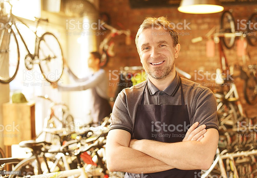 bike shop owner stands proudly in front of his stock stock photo