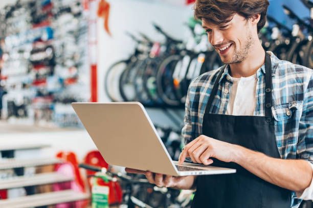 Bike shop owner with laptop Cheerful young mechanic using laptop in his bike shop bicycle shop stock pictures, royalty-free photos & images