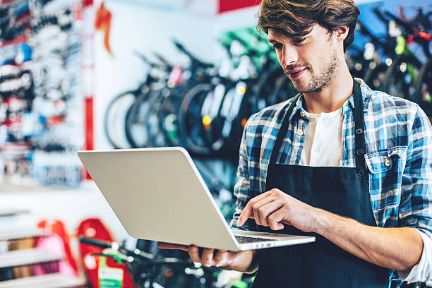Bike shop owner working on a laptop Young man working on a laptop in a bike shop. bicycle shop stock pictures, royalty-free photos & images