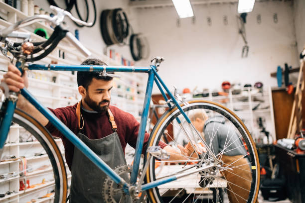 bike shop owner working on vintage bicycle - small business owner stock pictures, royalty-free photos & images