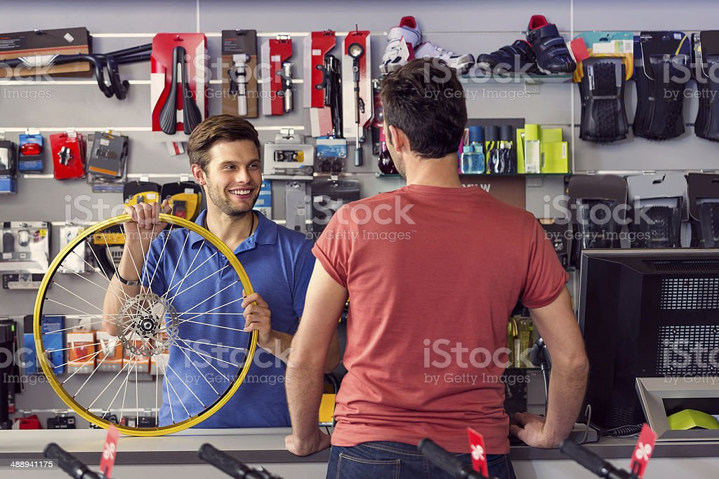 Bike store Sales clerk holding a bicycle wheel and talking with customer in bike store. Adult Stock Photo