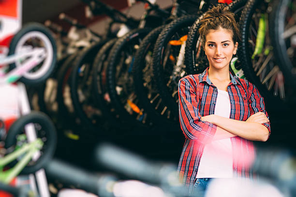 Bike store Portrait of a young female bicycle mechanic standing in her shop. bicycle shop stock pictures, royalty-free photos & images