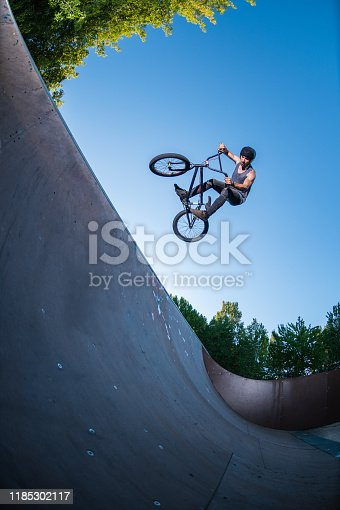 Biker jump high from jump box ramp performing table top trick.