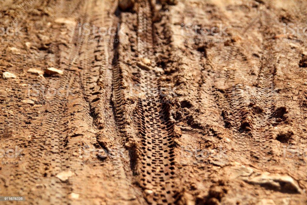 Marcas de pneu de bicicleta na realeza trilha enlameada. Marcas de pneu na estrada enlameada molhada, abstrato, material de textura. Pneu faixa na sujeira de areia ou lama, Tom retrô, Tom grunge, dirigir na areia, fora da pista de estrada. foto royalty-free