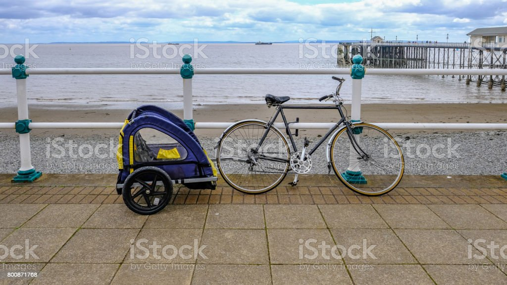 Bike with child trailer, secured to railing stock photo