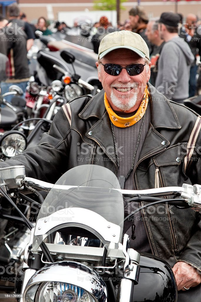 Biker at rally sitting on motorcycle and smiling stock photo