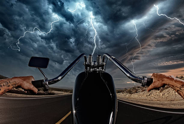 Biker Celebrating Freedom and Victory in Storm desert POV stock photo