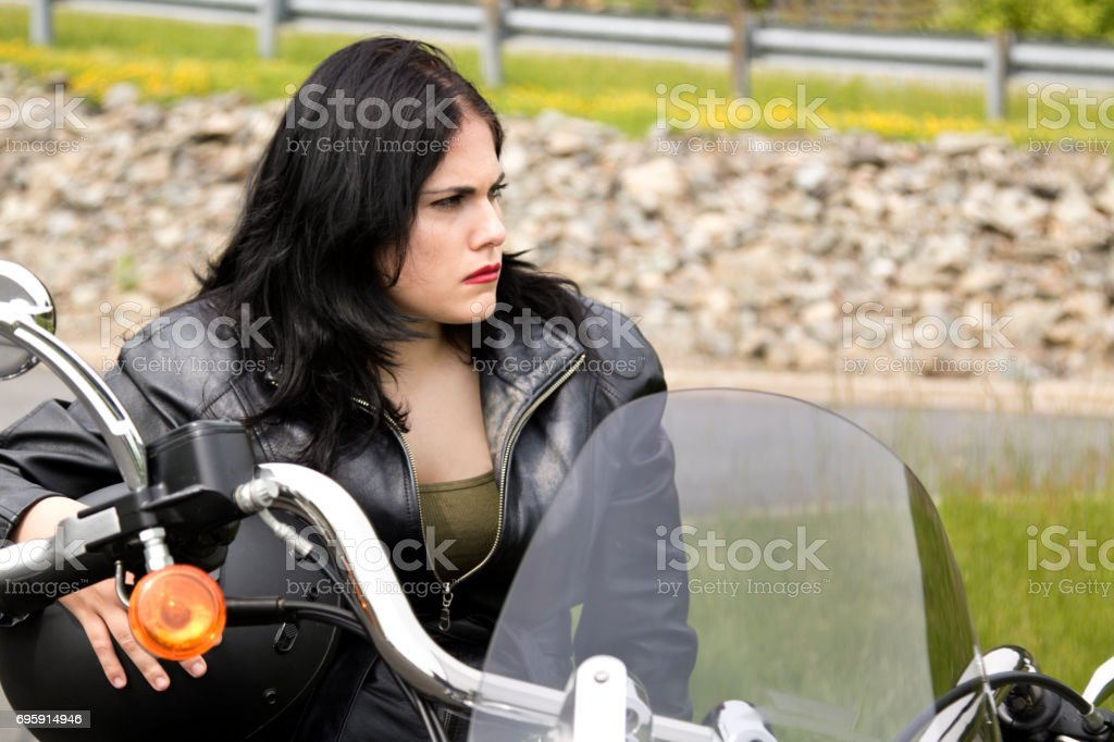 Biker Chick sitting on a motorcycle looking to left with a tough stare stock photo