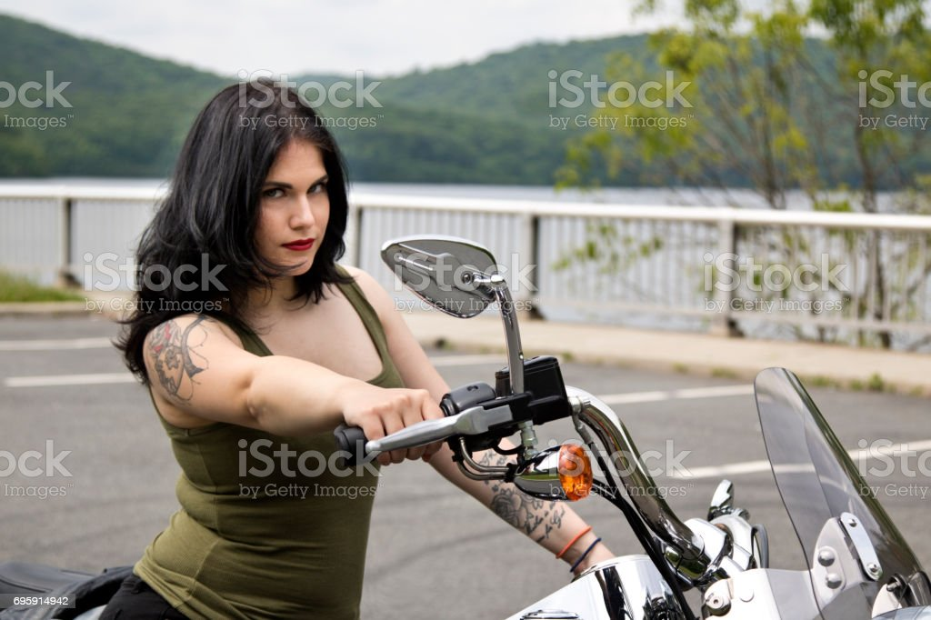 Biker Chick smiling on a motorcycle looking in to camera, looking pretty stock photo