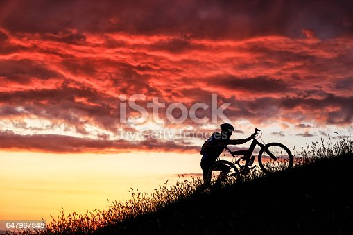 Silhouette of mountain biker moving up at sunset.