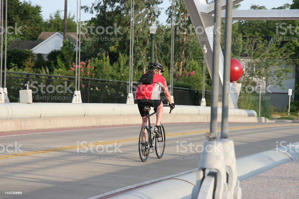Biker crossing a suspension bridge in Houston, Texas royalty-free stock photo