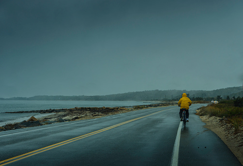 Biker cycling on the beach road in rainy weather. Passenger's view from a moving vehicle.