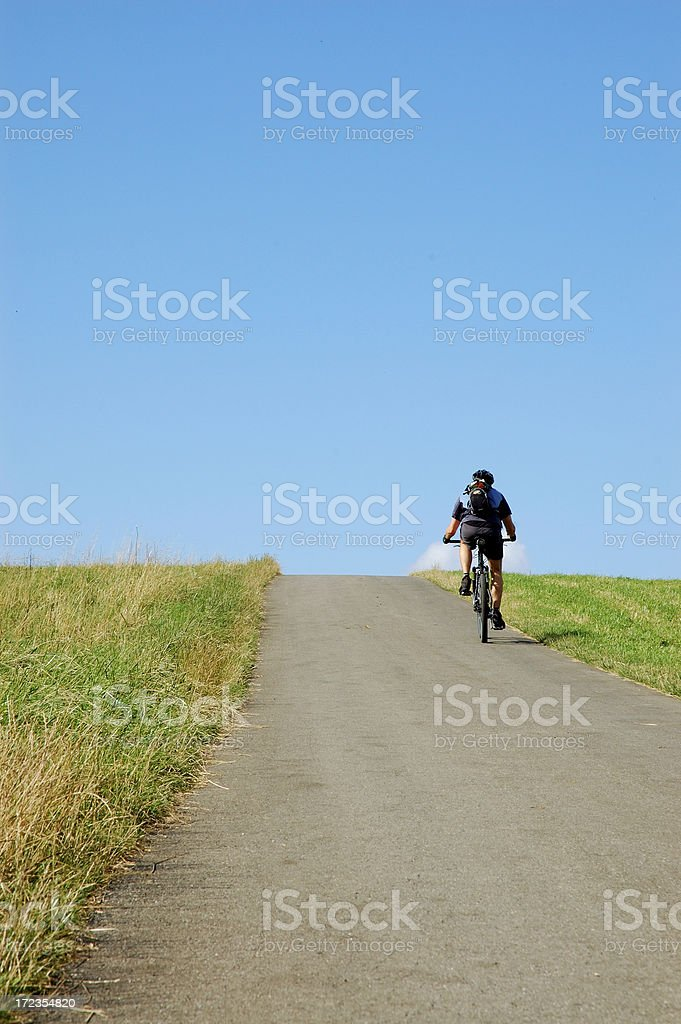 Biker cycling up a Hill royalty-free stock photo
