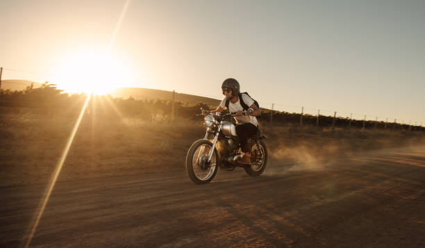 Biker driving a vintage motorcycle on dirt road Male biker driving a vintage motorcycle on dirt road. Man riding fast on his bike on countryside road. motorcycles stock pictures, royalty-free photos & images
