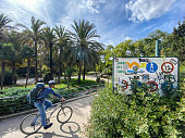 Valencia, Spain - October 5, 2020: Biker entering the Turia Garden. This huge public park, a dried riverbed, is the preferred way to cross the city for cyclists and people using push scooters and avoid the city traffic