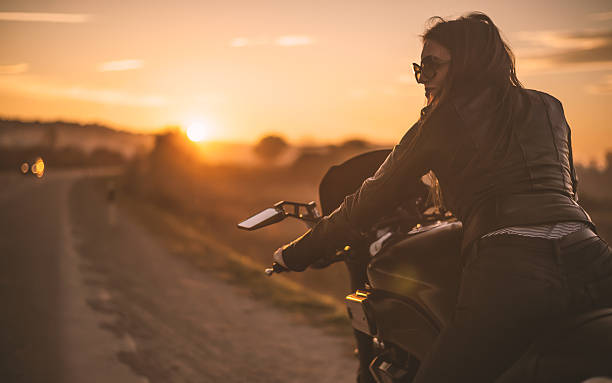 biker girl on the road - biker stock photos and pictures