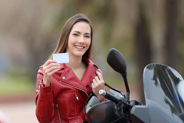 biker-girl zeigt eine leere kreditkarte - führerschein stock-fotos und bilder