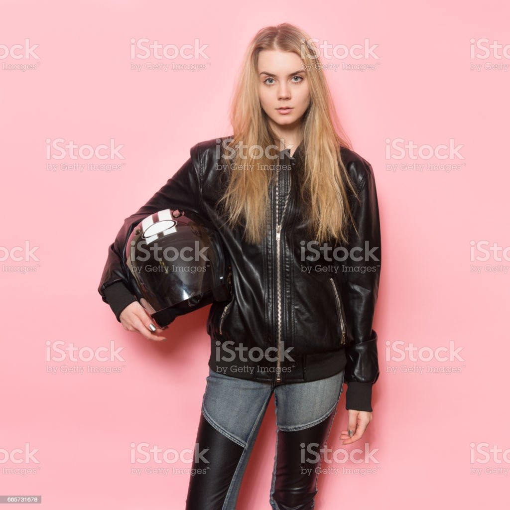 Biker girl wearing black leather jacket holding motorcycle helmet stock photo