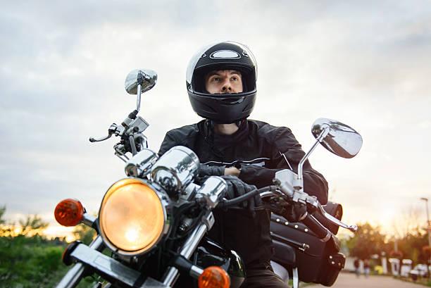 biker in helmet driving motorcycle on sunset. - biker stock photos and pictures