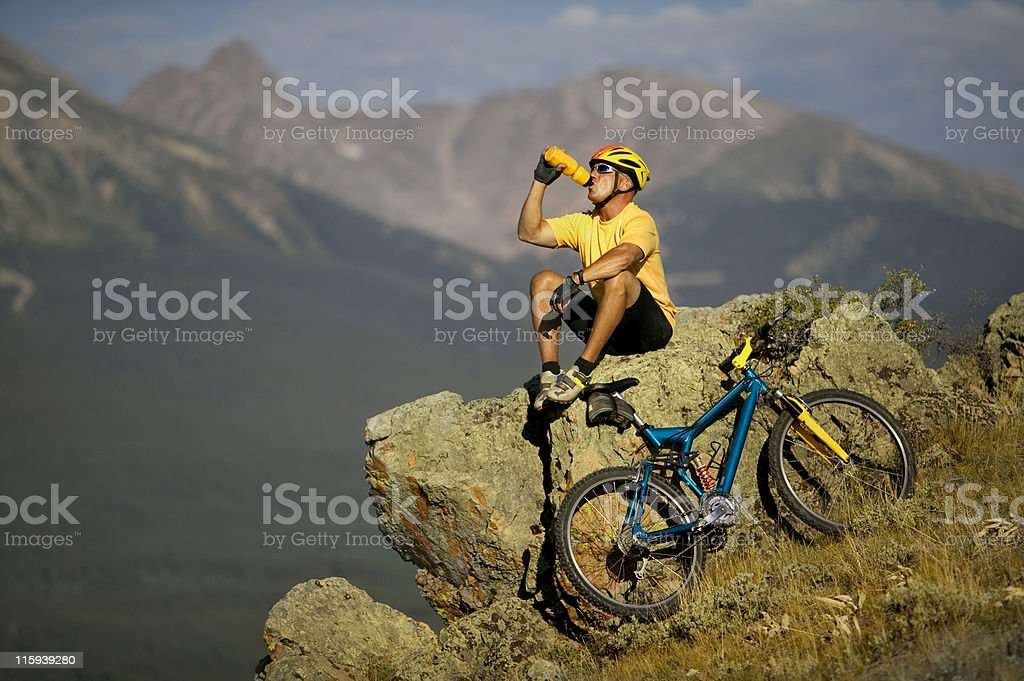 Biker in Mountains Drinking From Water Bottle royalty-free stock photo