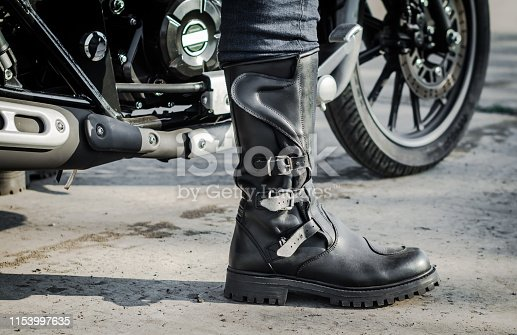 biker leg in a boot against the backdrop of a motorcycle
