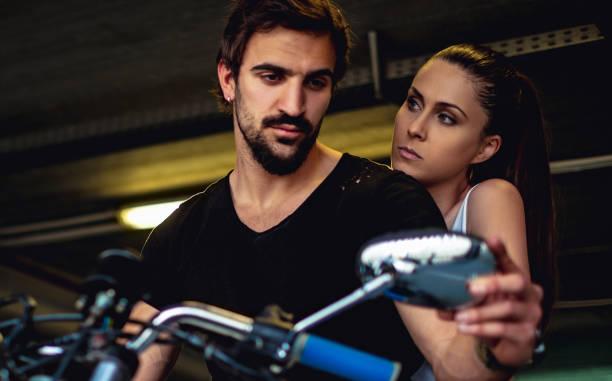 Biker mirando en el espejo mientras su novia está enfadada - foto de stock