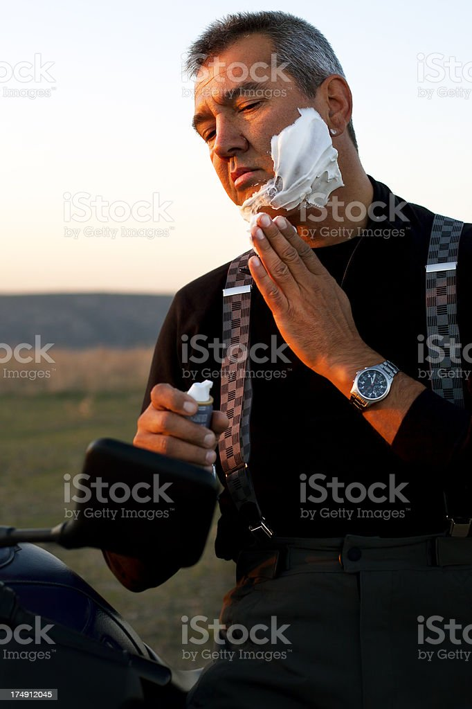 Biker Man Shaving on Motorcycle's Mirror royalty-free stock photo