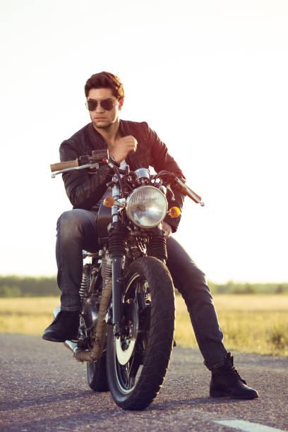 biker-mann sitzt auf einem fahrrad - motorrad männer stock-fotos und bilder