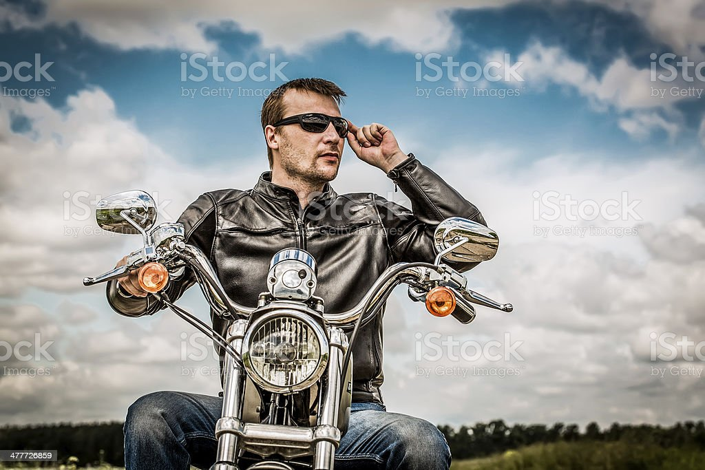 Biker man wearing a leather jacket and sunglasses sitting on his...