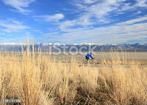 A biker rides on the roads circling the Island enjoying the views of snowcapped Wasatch Mountains in the distance.