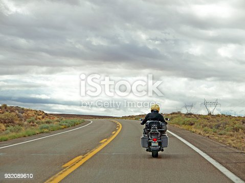 Lonely road with biker travelling through the Arizona desert landscape, dramatic sky ahead