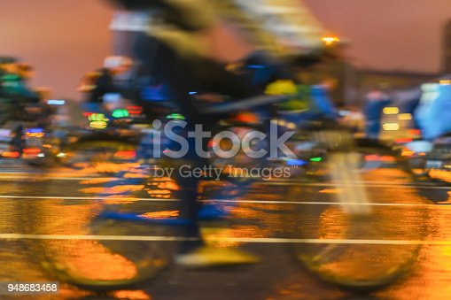 863454090 istock photo Biker on the bicycle, cyclist's foot on pedals close-up. Parade of bicyclists in city, night light, bokeh. Sport, healthy lifestyle concept. Abstract blurred background 948683458
