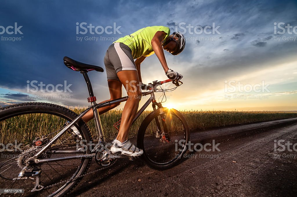 Biker on the meadow at the sunset against blue sky stock photo