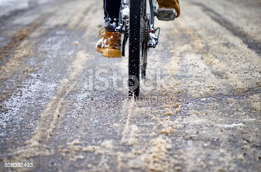 Biker on the road close up. Cloudy winter day. The road is in a small village in Romania. Film look image effect.