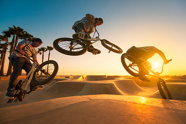 BMX Biker A sequence of a BMX biker at the bike at sunset. sequential series stock pictures, royalty-free photos & images
